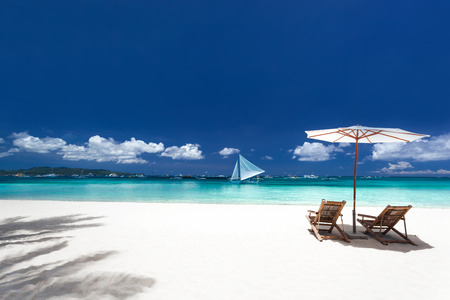 lounge chairs: Sun umbrellas and wooden beds on tropical beach. Caribbean vacation
