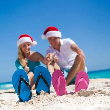 helpers: Caribbean Christmas vacation on sandy seashore. Two pair of flip flops standing in a sand on background with emotional happy couple in Santa Helpers hats, sitting on beach near beautiful turquoise sea, smiling and showing thumbs up. Focus on sandals. Stock Photo