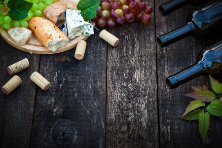 queso blanco: Botellas de vino con uva hojas sobre fondo de madera con espacio de copia, enfoque selectivo Foto de archivo