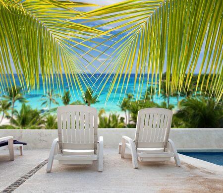Tropical vacation. Seaview from luxury resort balcony through palm tree leafs Standard-Bild