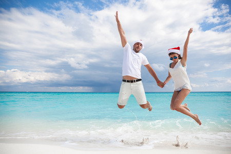 beach happy new year: Happy couple celebrating Christmas on beach, jumping in the air Stock Photo