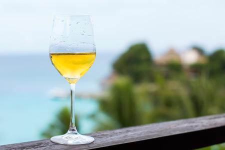 bahamas celebration: Glass of white wine on balcony rail, Tropical view Stock Photo