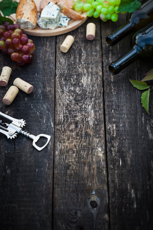 Wine bottles with grape leaves on wooden background with copy space, selective focus