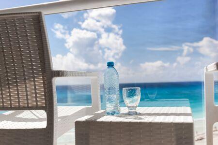 seaview: Balcony with plastic bottle of water on wicker table overlooking an ocean