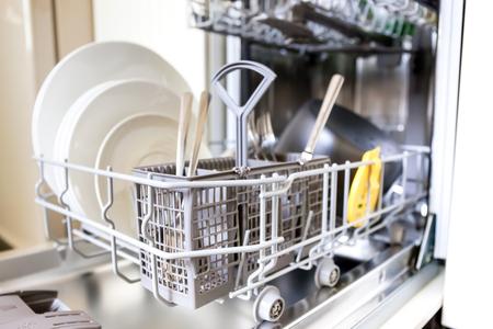 lavar trastes: Abra el lavaplatos con cristal y platos limpios, enfoque selectivo