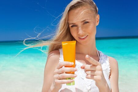 suncare: Portrait of woman holding suncare cream on beach, beauty concept