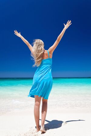 Happy blond girl on beach with outstretched arms, feeling freedom. Back view. Vacation concept photo