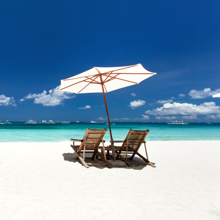 Sun umbrellas and wooden beds on tropical beach. Caribbean vacation