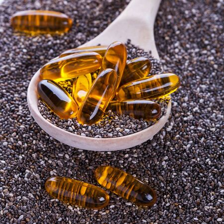 vegetal: Superfood for vegans - chia seeds powerful of vegetal Omega-3 oil. Soft gel pills in wooden spoon on dry chia seeds background, selective focus