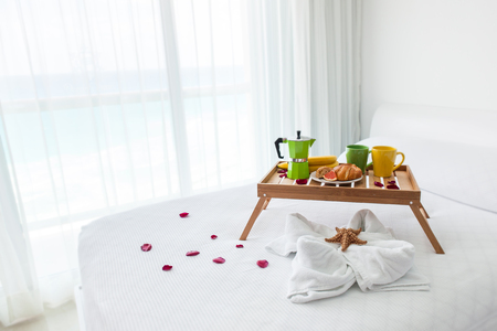 continental breakfast: Breakfast wooden tray with coffee percolator and croissant on bed, decorated starfish on white towel