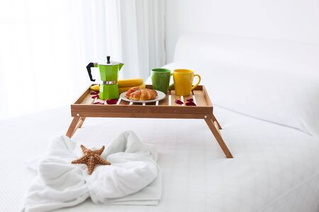hotel resort: Breakfast wooden tray with coffee percolator and croissant on bed, decorated starfish on white towel