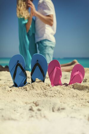 kneeled: Pair of color flip flops on sandy beach near sea with romantic couple on background. Focus on slippers, warm toned image. Happy travel concept