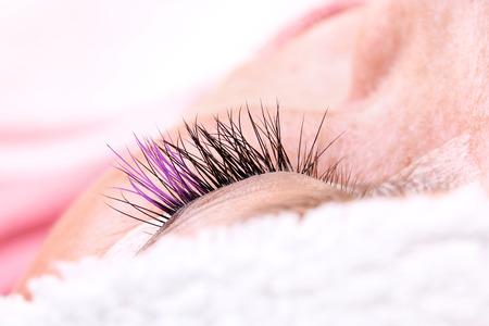 Lash making process, extreme long lashes with closed eye, woman eyelash extension. Macro shot, shallow depth