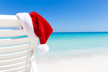 sombrero: Santa Claus Hat on sunbed near  sandy beach with turquoise caribbean sea water. Tropical Christmas Card