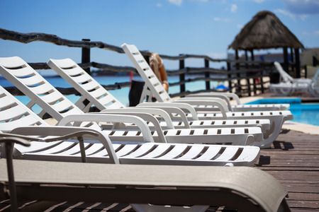 near: Lounge sunbeds near swimming pool, outdoor near caribbean sea Stock Photo