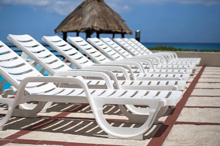 sunbeds: Lounge sunbeds near swimming pool, outdoor near caribbean sea Stock Photo