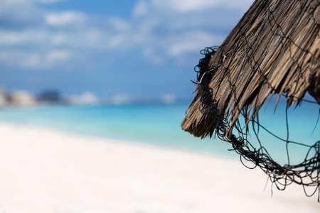 sun umbrella: Grass leaf palm sun umbrella with caribbean sea background Stock Photo