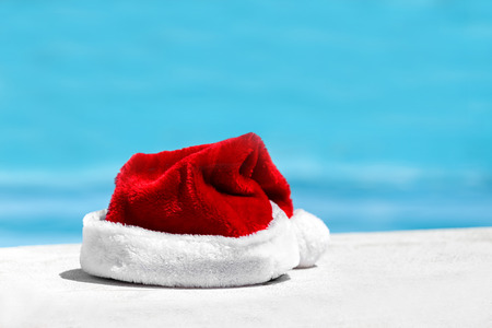 Santa Claus hat near swimming pool with clean turquoise water