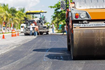 La construcción de carreteras trabaja con la máquina aplanadora y consumador de asfalto