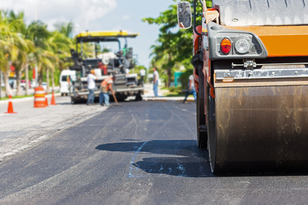 Road construction works with steamroller machine and asphalt finisher Stock Photo