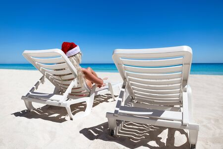 Woman in Santa Claus Hat sitting on sunbed at caribbean sandy beach with turquoise sea water and white sand