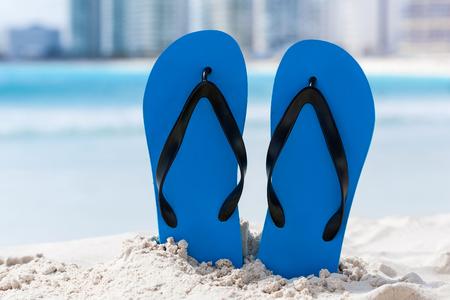 white sand: Vibrant color flip flops in white sand on sea background