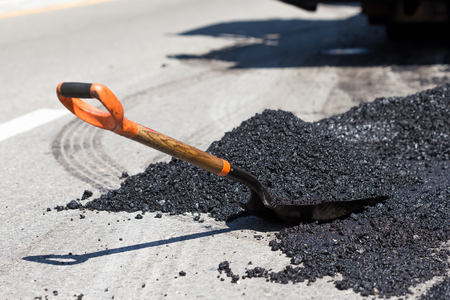 steam roller: Shovel for road construction works in a heap of new asphalt at street