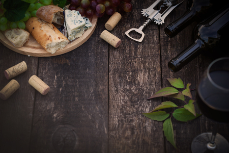 dark wood: Wine bottles with grape leaves on wooden background with copy space, toned image Stock Photo