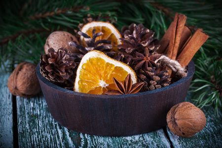 decoration: Christmas decoration card with evergreen fir tree, cones, cinnamon on rustic wooden background. Selective focus, shallow dof Stock Photo