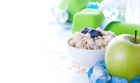 Fitness frame with energy breakfast, oatmeal, apple and mineral water with sport tools on background. Healthy lifestyle concept with copy space.