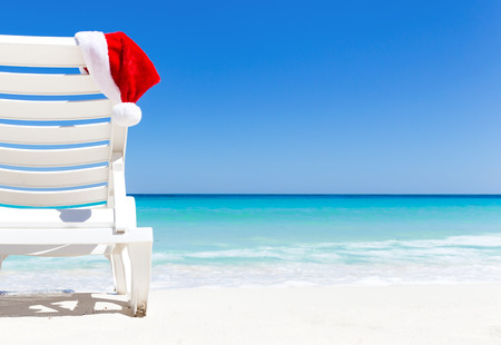 Santa Hat on sunbed near  tropical calm beach with turquoise caribbean sea water and white sand. Christmas vacation concept