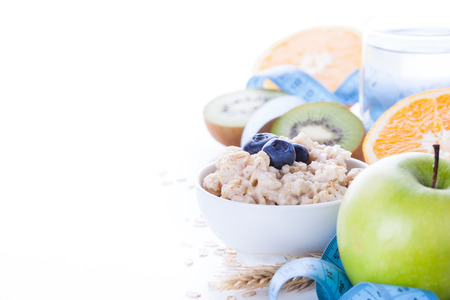 Morning healthy nutrition, diet frame with oatmeal porridge, fruits, mineral water and measuring tape. Perfect breakfast before workout Standard-Bild