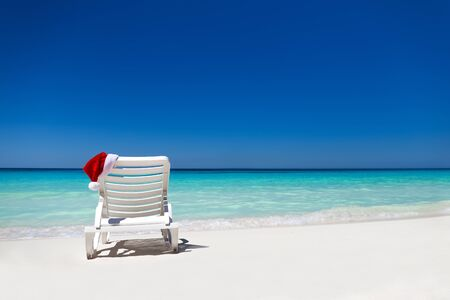 christmas concept: Santa Claus Hat on sunbed near  tropical calm beach with turquoise caribbean sea water and white sand. Christmas vacation concept Stock Photo