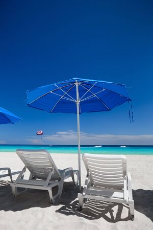 sun umbrellas: Caribbean beach with blue sun umbrellas and white beds. Tropical vacation Stock Photo