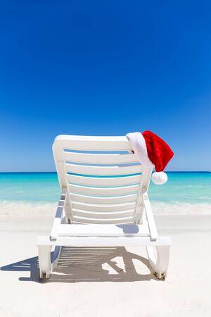 tropical christmas: Santa Claus Hat on sunbed near  sandy beach with turquoise caribbean sea water. Tropical Christmas Card
