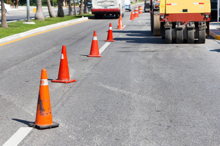 Road construction works. Traffic cones at tropical street warning about asphalt pavement works Stock Photo
