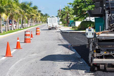 asphalt paving: Pavement truck laying fresh asphalt  during tropical road construction Stock Photo