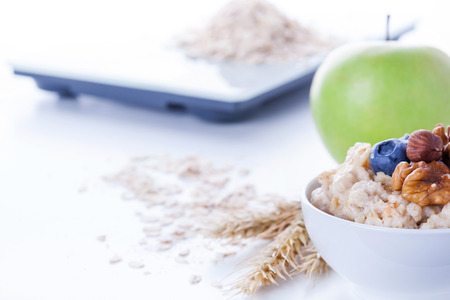 carbohydrates: Electronic digital kitchen scale with oatmeal, apple and measuring tape. Healthy nutrition concept Stock Photo