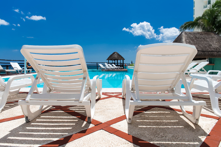 sunbeds: Lounge sunbeds near swimming pool. Tropical vacation concept Stock Photo