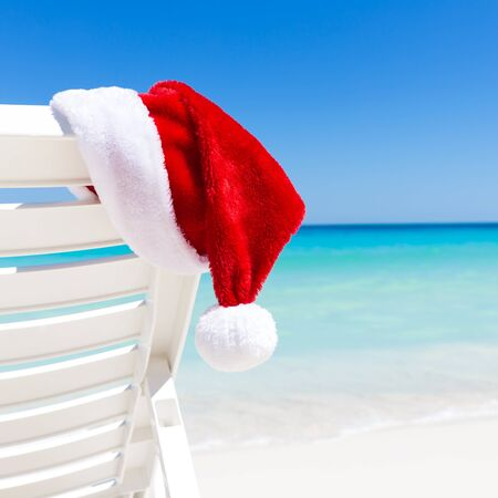 santa hat: Santa Claus Hat on sunbed near  tropical calm beach with turquoise caribbean sea water and white sand. Christmas vacation concept Stock Photo
