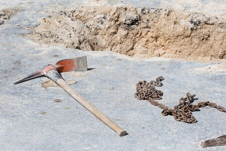 dug well: Road repair construction. Mattock and chain on asphalt
