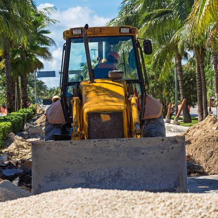 roadwork: Roadwork construction. Bulldozer repairing road at tropical street Stock Photo