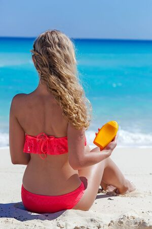 no face: Blond tan woman on summer vacation is sitting on beach near turquoise sea and holding sunscreen lotion in hand, back view, no face, focus on cream tube. Healthy tanning concept. Stock Photo