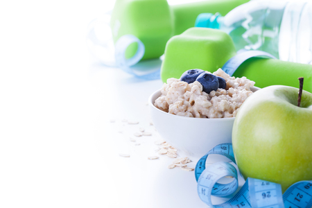 minerals: Fitness frame with energy breakfast, oatmeal, apple and mineral water with sport tools on background. Healthy weight loss concept with copy space.