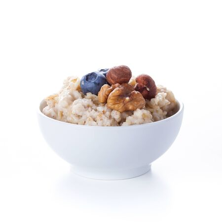 oatmeal bowl: Oatmeal porridge in bowl topped with fresh blueberries, nuts and honey on white background Stock Photo