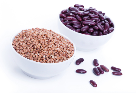 source of iron: Dry buckwheat and black beans in white bowl, source of Iron (Fe) Stock Photo