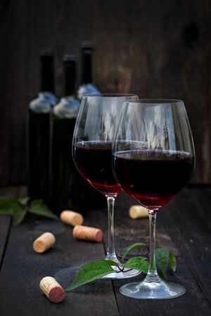 closed corks: Glass of red wine with corks on old wooden table