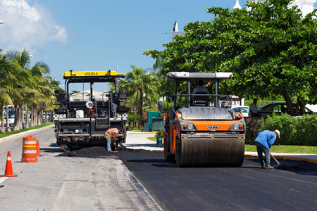 steamroller: Mexico, Cancun - 10 October 2015: Road construction works with steamroller machine and asphalt finisher
