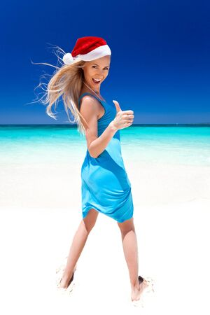 Happy blond girl in Santa hat on tropical beach, showing thumbs up. Christmas Vacation photo