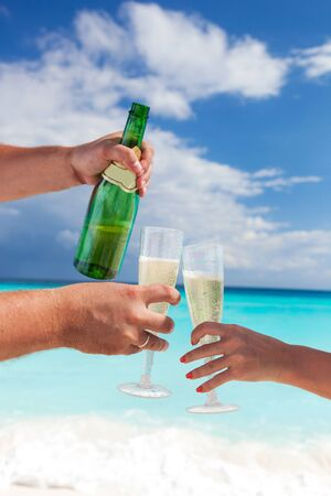 champers: Toast champagne on beach with caribbean sea background, Two flute champagne glasses in hands, close up. Celebrating holidays Stock Photo